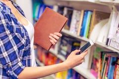 Menina com o dispositivo na livraria Foto de Stock