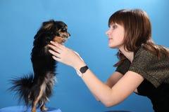 A menina com o doggie em um fundo azul Imagens de Stock Royalty Free