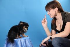 A menina com o doggie em um fundo azul Fotografia de Stock Royalty Free
