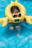 Menina com o flutuador amarelo do brinquedo do caranguejo na associação do quintal fotografia de stock royalty free