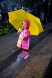 Menina com o guarda-chuva amarelo que joga na chuva 2 Fotografia de Stock Royalty Free