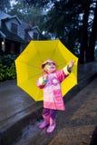 Menina com o guarda-chuva amarelo que joga na chuva 3 Imagem de Stock