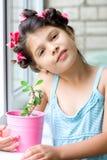 Menina com o houseplant no potenciômetro cor-de-rosa Imagens de Stock