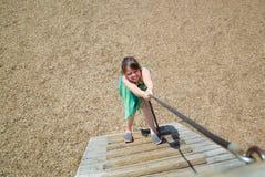Menina com o jogo engraçado das expressões da cara, escalando acima no escadas de madeira fotos de stock
