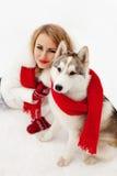 Menina com o lenço vermelho que senta-se com um cão de puxar trenós Siberian na neve foto de stock royalty free