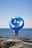 Menina com o lilo na praia rochosa Lilo tem reciclar o símbolo Foto de Stock