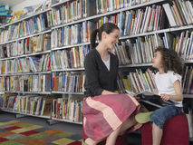 Menina com o livro de ensino da história da leitura na biblioteca fotos de stock royalty free