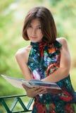 Menina com o livro no parque Fotos de Stock Royalty Free