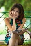 Menina com o livro no parque Imagem de Stock