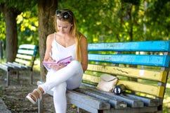 Menina com o livro no parque Foto de Stock