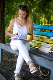 Menina com o livro no parque Fotografia de Stock