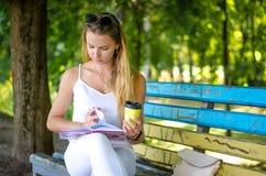 Menina com o livro no parque Foto de Stock Royalty Free