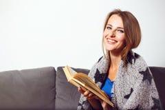 Menina com o livro no sofá Fotografia de Stock
