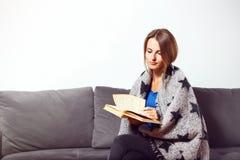 Menina com o livro no sofá Imagem de Stock