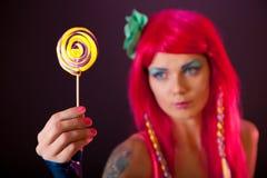 Menina com o lollipop cor-de-rosa da terra arrendada do cabelo Fotos de Stock Royalty Free