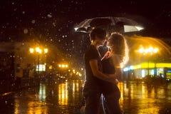 A menina com o menino que beija sob uma chuva do para baixo-derramamento Fotografia de Stock Royalty Free