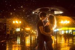 A menina com o menino que beija sob uma chuva do para baixo-derramamento Foto de Stock