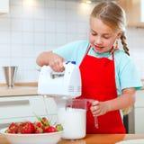 Menina com o misturador na cozinha Foto de Stock