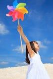 Menina com o pinwheel na praia fotografia de stock royalty free