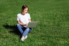 menina com o portátil no parque fotos de stock royalty free