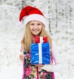 Menina com o presente e o chapéu de Santa que mostram os polegares acima na floresta do inverno Foto de Stock