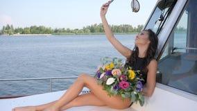 A menina com o ramalhete das flores faz o selfie no barco de vela no resto do verão no mar vídeos de arquivo