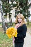 Menina com o ramalhete das folhas em um parque Imagem de Stock Royalty Free