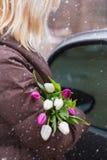 Menina com o ramalhete das tulipas em um dia nevado que está o carro próximo Fotografia de Stock Royalty Free