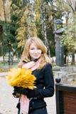 A menina com o ramalhete do amarelo sae no parque Imagens de Stock Royalty Free