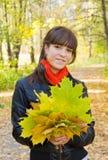 Menina com o ramalhete do outono no parque Imagens de Stock Royalty Free