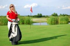 Menina com o saco de golfe no campo de golfe Imagens de Stock Royalty Free