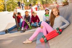 Menina com o skate e os amigos que sentam-se atrás Fotografia de Stock Royalty Free