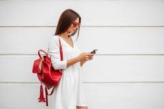 Menina com o smartphone na rua imagem de stock