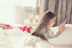 Menina com o tablet pc na cama Foto de Stock Royalty Free