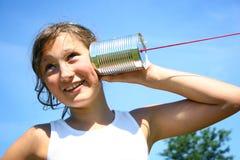 Menina com o telefone da lata de estanho fotos de stock