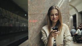 Menina com o telefone esperto no estação de caminhos-de-ferro Retrato de uma mulher caucasiano nova, olhando o telefone ao espera vídeos de arquivo