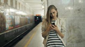 Menina com o telefone esperto no estação de caminhos-de-ferro Retrato de uma mulher caucasiano nova, olhando o telefone ao espera filme