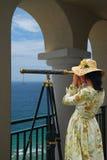 Menina com o telescópio sob arcos Imagens de Stock Royalty Free