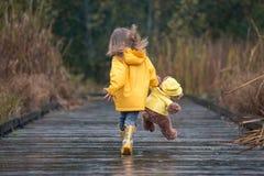 Menina com o urso de peluche em combinar as capas de chuva amarelas que correm no Fotografia de Stock Royalty Free
