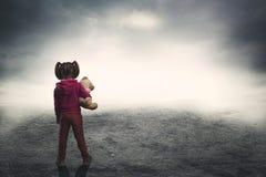Menina com o urso do brinquedo na escuridão Imagens de Stock Royalty Free
