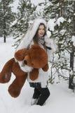 A menina com o urso na floresta do inverno Foto de Stock Royalty Free