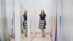 Menina com o vestido de tentativa do cabelo vermelho perto do espelho em sala apropriada - conceito da compra fotos de stock