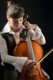 Menina com o violoncelo no fundo preto Foto de Stock