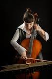 Menina com o violoncelo no fundo preto Fotos de Stock