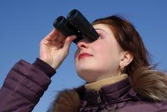 Menina com olhares surpreendidos através dos binóculos Fotografia de Stock