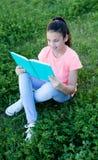Menina com olhos azuis que lê um livro fora Imagens de Stock