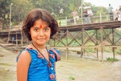 A menina com olhos bonitos e o tilak assinam o jogo na vila indiana Fotos de Stock