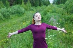 Menina com olhos fechados e os braços largamente espalhados imagem de stock royalty free