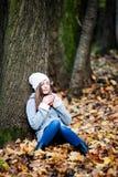 Menina com olhos fechados e um copo do chá em suas mãos Fotos de Stock Royalty Free