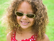 Menina com os óculos de sol desgastando de um sorriso brilhante Foto de Stock